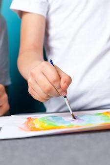 Close up do menino pintura aquarela lição de casa para o jardim de infância na superfície azul