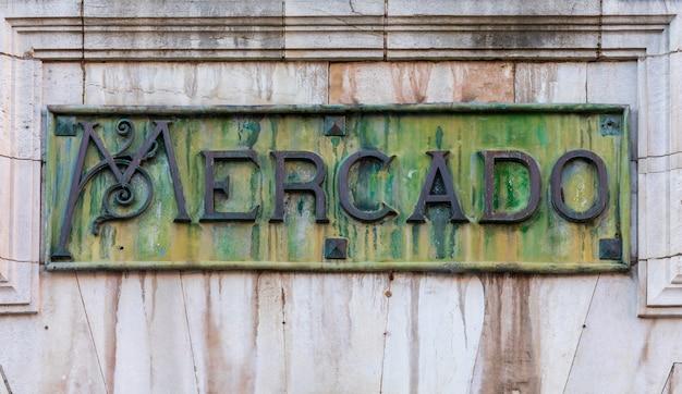 Close-up do mercado de abastos, em espanhol. em bronze oxidado, com tons de verde e ocre.