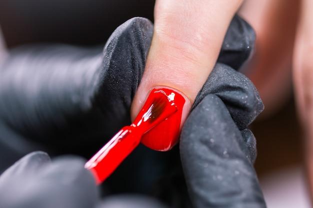 Close up do mestre em luvas de borracha cobrindo as unhas vermelhas com um casaco de acabamento no salão de beleza