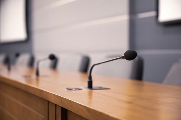 Close-up do microfone de conferência na mesa de reunião.