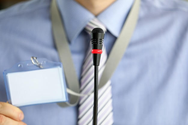 Close-up do microfone moderno. indivíduo do sexo masculino segurando crachá com informações pessoais.