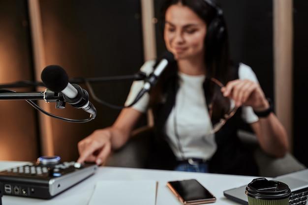Close-up do microfone no estúdio jovem apresentadora de rádio moderando um programa ao vivo no fundo