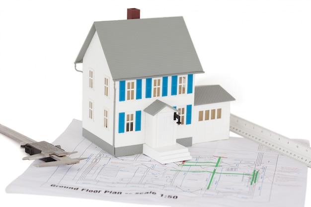 Close up do modelo de casa de brinquedo e pinça em um plano de piso térreo