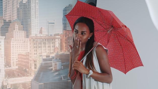 Close-up do modelo preto sorridente, posando com guarda-chuva vermelho na cadeira alta bar para sessão de fotos de revista de moda