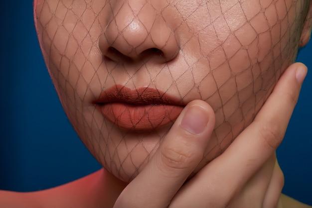 Close-up do nariz e boca de mulher irreconhecível, posando no estúdio com arrastão, cobrindo o rosto