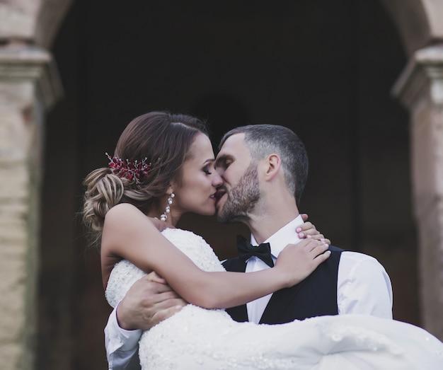 Close-up do noivo segurando uma noiva linda