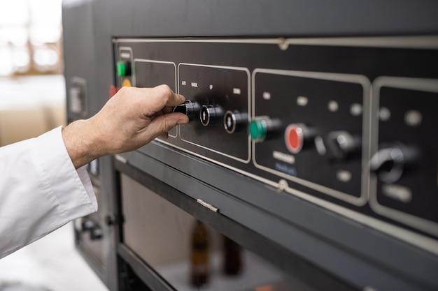 Close-up do operador da máquina irreconhecível girando o botão do painel de controle em uma loja industrial