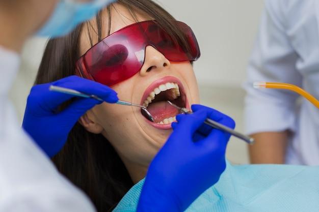 Close-up do paciente recebendo procedimento com dentistas