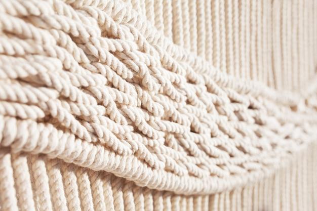 Close-up do padrão de textura macramé feito à mão. eco amigável tricô moderno diy conceito de decoração natural no interior. macramê artesanal 100% algodão. passatempo feminino.
