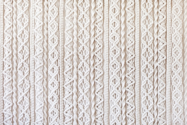 Close-up do padrão de textura macramé feito à mão. eco amigável tricô moderno diy conceito de decoração natural no interior. postura plana. macramê feito à mão 100% algodão. passatempo feminino.