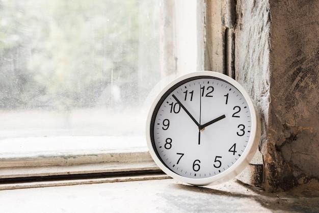 Close-up do pequeno relógio redondo branco perto da janela de vidro
