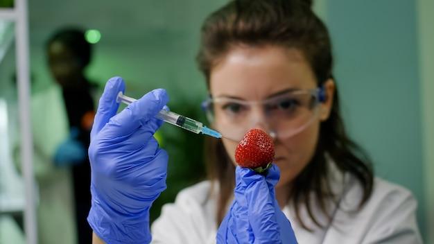 Close-up do pesquisador bioquímico injetando morango saudável com líquido de dna usando seringa médica, verificação de teste genético. biólogo cientista examinando frutas em laboratório agrícola de microbiologia