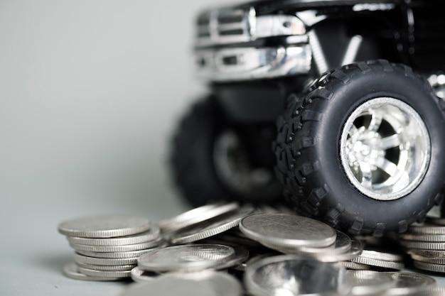 Close-up do pneu da pick-up do carro em miniatura em pilhas de moedas