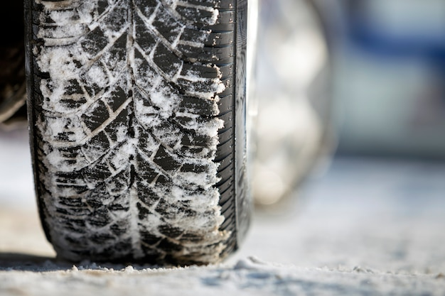 Close-up do pneu de borracha das rodas de carro na neve profunda. transporte e conceito de segurança.