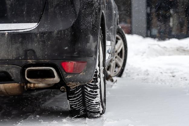 Close-up do pneu de borracha de rodas de carro em neve profunda, conceito de transporte e segurança, vista traseira