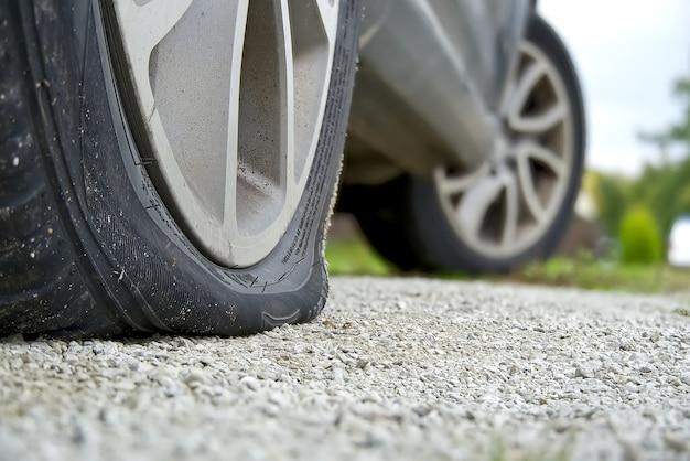 Close-up do pneu traseiro furado no carro. o weel traseiro direito quebrado. rodas traseiras danificadas no lugar de estacionamento.