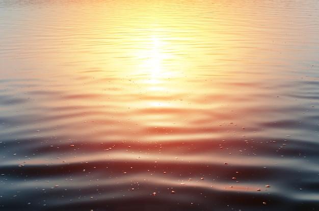 Close-up do pôr do sol no mar. superfície calma de água azul escura e reflexo amarelo-avermelhado do sol, ao ar livre. paisagem de fundo do mar, lago, lagoa com espuma. espaço de cópia de pano de fundo natural, sem pessoas