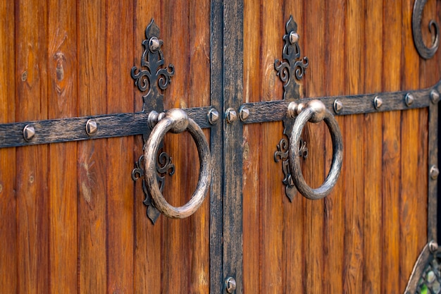 Close-up do portão de madeira com elementos de ferro forjado.