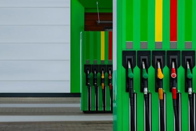 Close-up do posto de gasolina com mangueiras de combustível coloridas.
