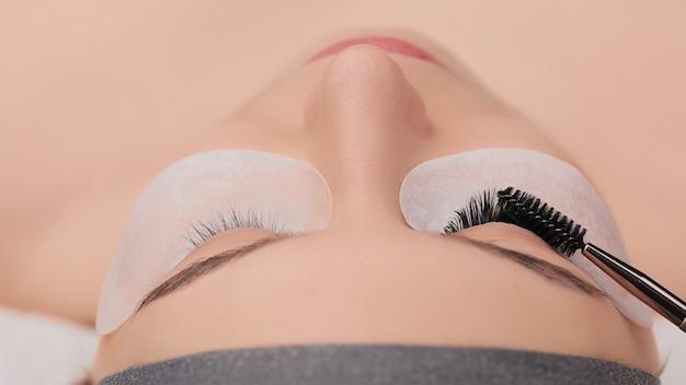 Close-up do procedimento de extensão dos cílios. pestanas falsas. conceito de maquiagem e beleza.
