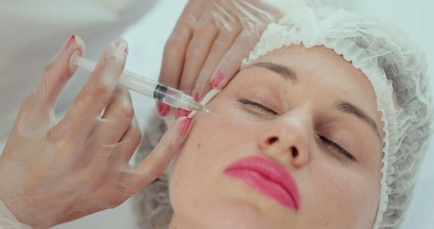Close-up do procedimento de injeção de beleza em clínica de beleza moderna. injeção com seringa na bochecha feminina. esteticista realizando mesoterapia e tratamento de lifting facial em salão de beleza.