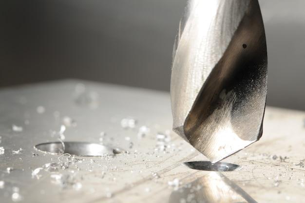 Close-up do processo de perfuração e lascas de metal