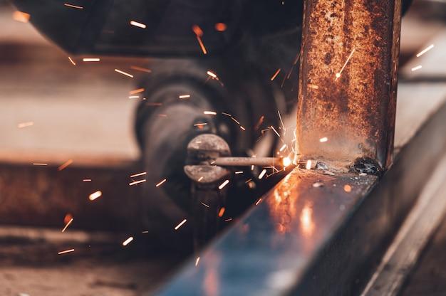 Close-up do processo de soldagem de duas peças metálicas. fundo industrial.