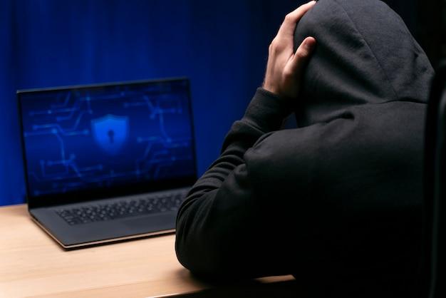 Close-up do programador na mesa com o laptop