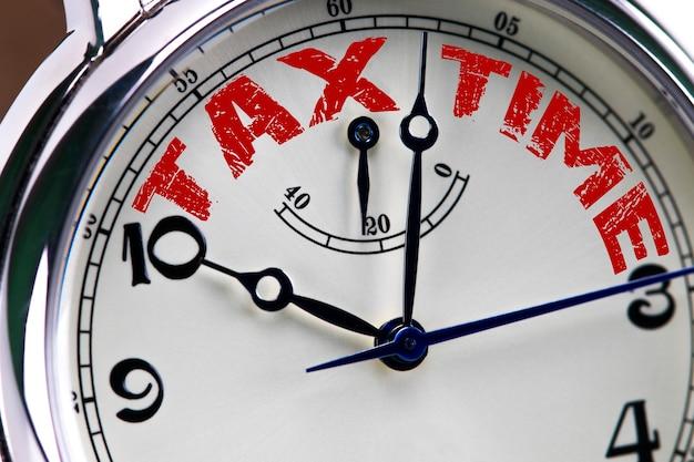 Close up do relógio do conceito do tempo do imposto isolado no fundo branco com palavras vermelhas.