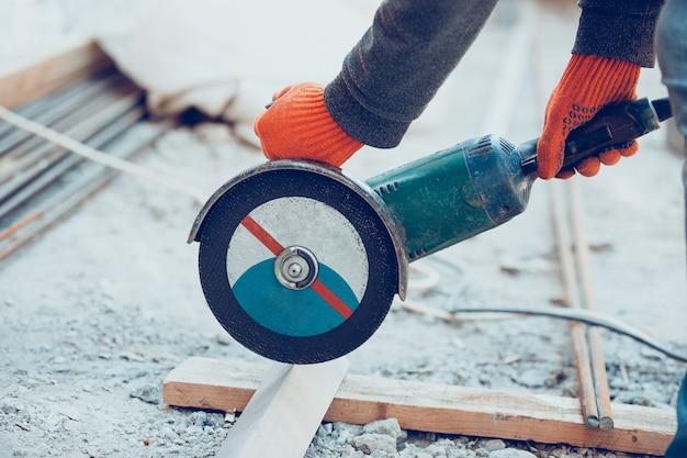 Close-up do reparador de uniforme, construtor profissional, trabalhando com equipamentos de construção. processo de construção, renovação de apartamento, reparação, construção. serrar, conectar, cortar, preparar.