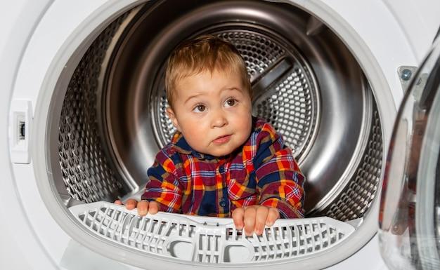 Close up do retrato adorável criança olha para fora da máquina de lavar, conceito engraçado