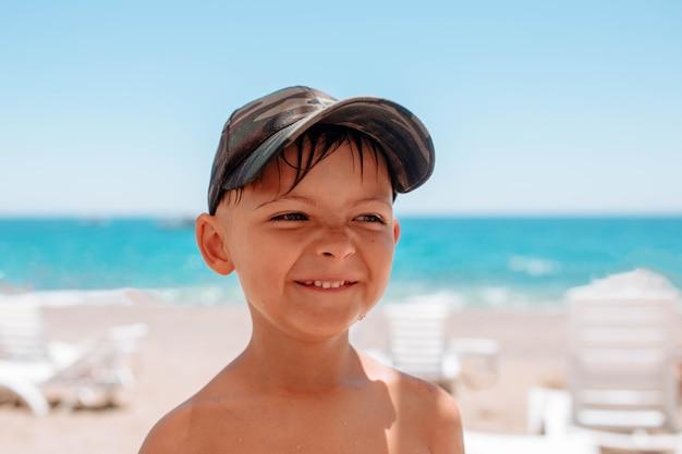 Close-up do retrato de um menino que sorri sinceramente na costa do mar. as férias de verão em países quentes são uma alegria para as crianças.