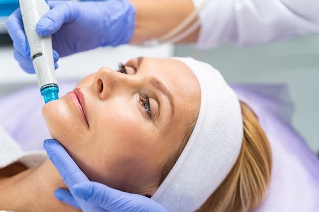 Close-up do retrato de uma paciente de meia-idade submetida a um tratamento facial de peeling de microdermoabrasão hidro vácuo