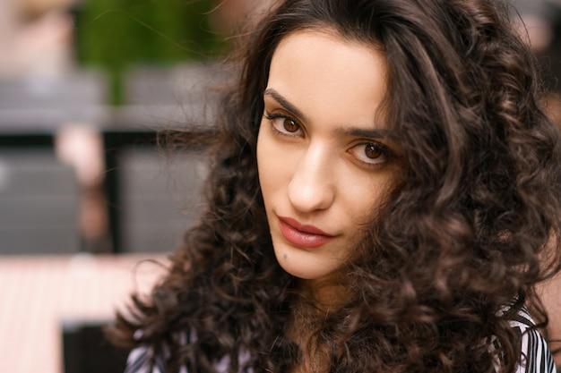 Close-up do retrato feminino, olhos castanhos escuros de cabelo encaracolado, posando na rua. linda mulher morena