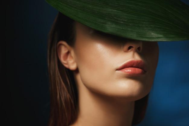 Close up do rosto da coberta da jovem mulher atrás da folha verde fresca.