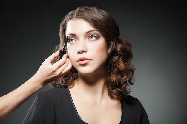 Close-up do rosto da mulher com escova de rímel sobre fundo escuro