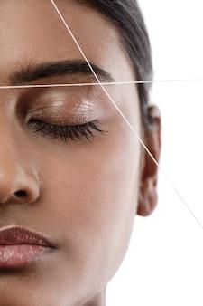 Close-up do rosto de uma mulher indiana com um fio. rosqueamento da sobrancelha - procedimento de depilação para correção do formato da sobrancelha