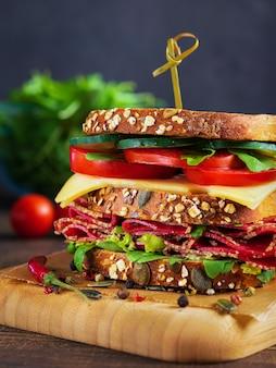 Close-up do sanduíche delicioso com salame, queijo e os legumes frescos.