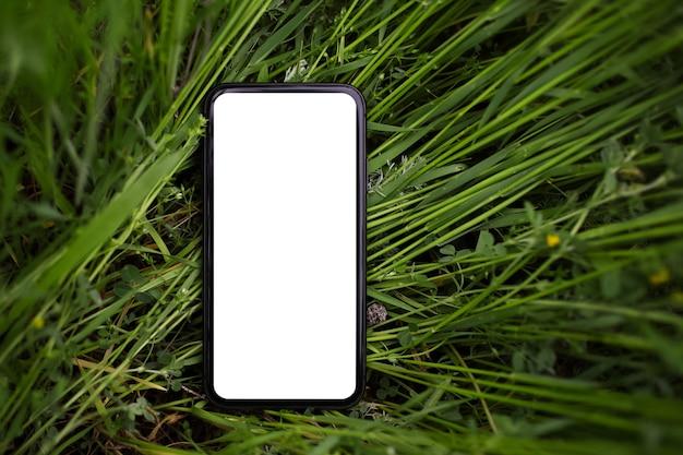 Close-up do smartphone com maquete na grama verde. vista do topo.