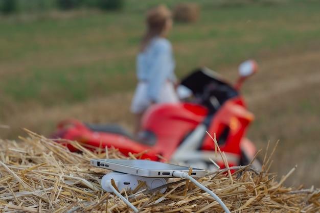 Close-up do smartphone com um carregador portátil. power bank carrega o telefone tendo como pano de fundo uma motocicleta, uma garota e a natureza.