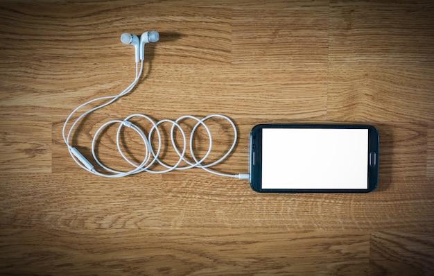 Close up do smartphone preto com tela branca com fones de ouvido na superfície de madeira