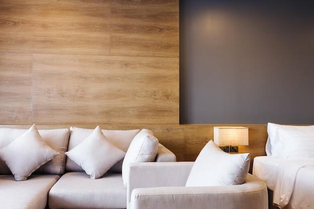 Close-up do sofá e do descanso branco na decoração da cama com a lâmpada leve no interior do quarto do hotel.