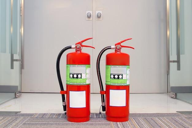 Close-up do tanque de extintores de incêndio vermelho na porta de saída de emergência.