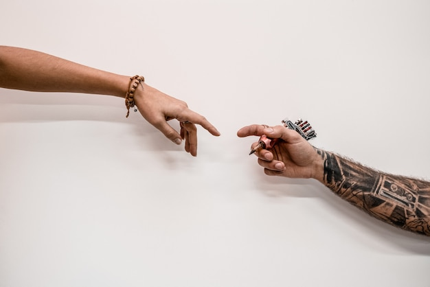 Close-up do tatuador de hipster antiquado de duas mãos segurando a máquina de tatuagem em um fundo branco.