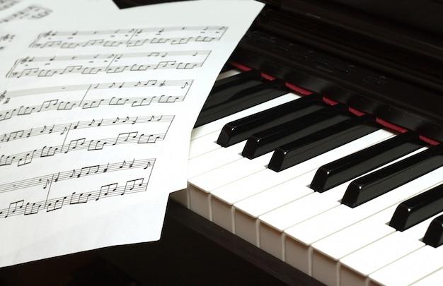 Close-up do teclado de piano e partituras