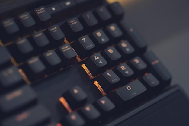 Close-up do teclado para jogos rgb de computador, iluminado por led colorido