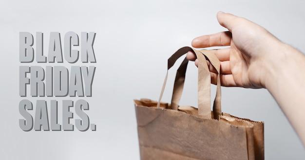 Close-up do texto preto de vendas sexta-feira, sobre o fundo cinza perto de papel ecológico na mão masculina.