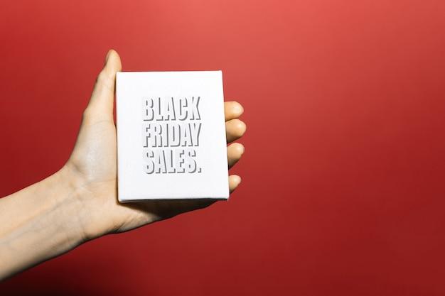 Close-up do texto preto sexta-feira em papel branco na mão feminina. fundo de cor vermelha.