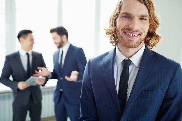 Close-up do trabalhador com barba por fazer sorrir