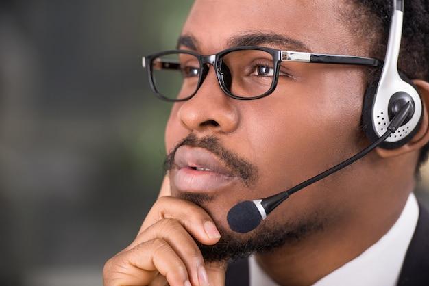 Close-up do trabalhador confiante com um fone de ouvido.